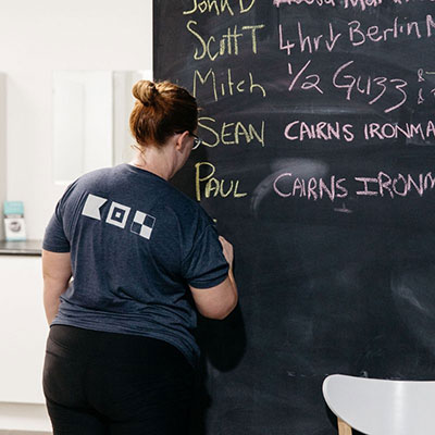 Woman writing down her fitness goals on a chalk board